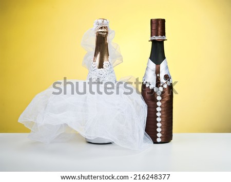 Souvenir bottles for a wedding on a yellow background.Figurines of the bride and groom.champagne