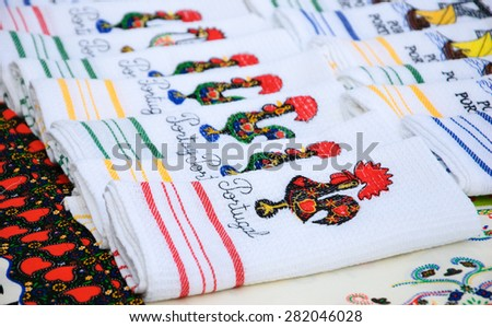 Souvenir towels with embroidery of the Galo de Barcelos (Barcelos Rooster) -  traditional symbol of Portugal - at the street market in Porto (Portugal). Selective focus on the closest towel. - stock photo