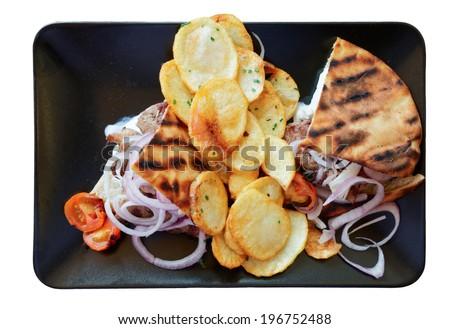 Souvlaki dish in black plate, isolated on white background - stock photo
