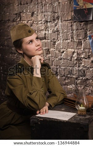 Soviet female soldier in uniform of World War II dreams - stock photo