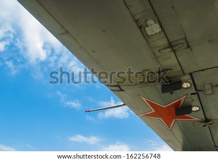 Soviet military aircraft with red star on the wings. Aircraft wing at sky background closeup.