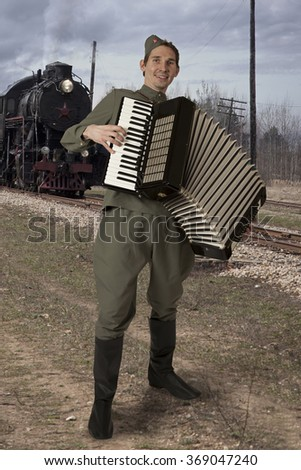 Soviet soldier dressed in uniform of World War II playing the accordion outdoors