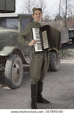Soviet soldier in uniform of World War II playing the accordion outdoors  - stock photo