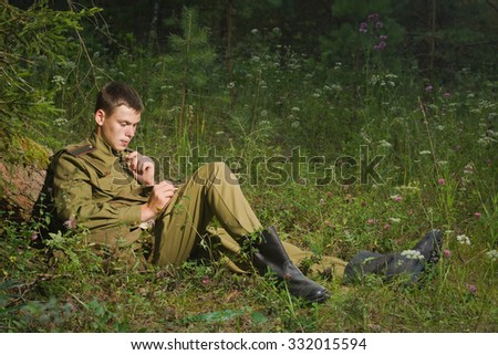 Soviet soldier in uniform of World War II writes a letter. No intellectual property