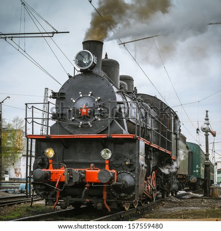 Soviet steam locomotive and the filling valve. - stock photo