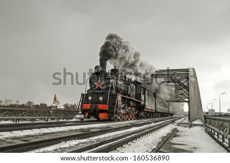 Soviet steam locomotive is moving over the bridge. - stock photo