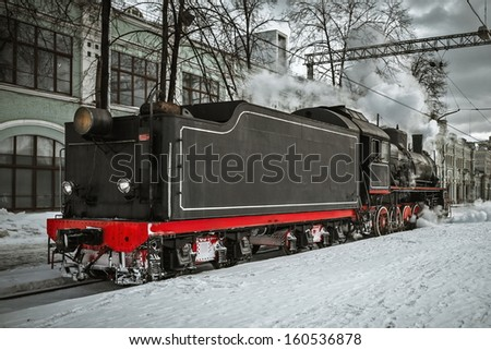 Soviet steam locomotive stands on the platform of the station.