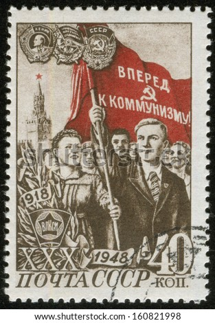"""SOVIET UNION - CIRCA 1948: A stamp printed by the Soviet Union Post is entitled """"40 years to Komsomol"""", entitled """"Komsomol at Fight for Culture"""". It shows a young couple holding books, circa 1948. - stock photo"""