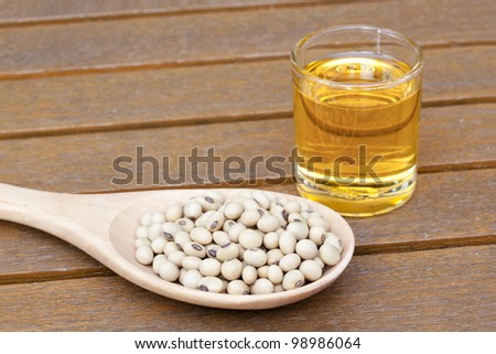 Soy bean and oil on a teak table - stock photo