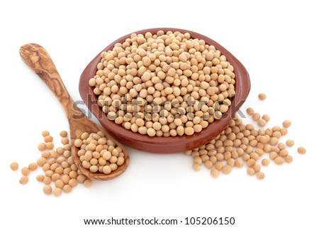 Soy bean pulses in a terracotta bowl, olive wood spoon and loose over white background. - stock photo
