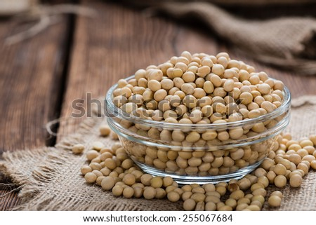 Soy Beans (detailed close-up shot) on rustic wooden background
