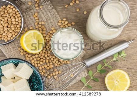 Soy mayonnaise, lemon, soybeans,tofu and metallic whip, on wooden background - stock photo