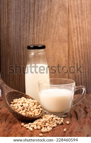 Soy milk and soy bean on wooden background - stock photo