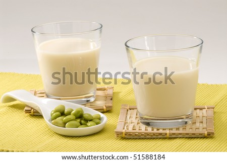 Soy milk in a glass. Fresh soy beans in foreground. White background. - stock photo