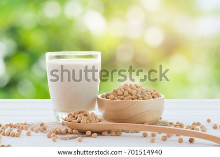 Soy milk in glass and soy bean on spoon it on white table background with lighting in the morning,healthy concept.