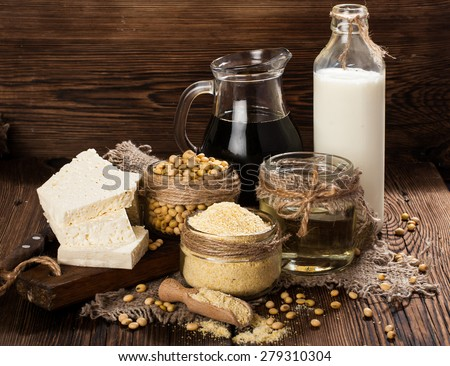 Soy products (soy flour, tofu, soy milk, soy sauce) on a wooden background. rustic style - stock photo
