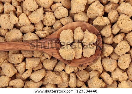 Soy protein chunks in an olive wood spoon and forming a background. - stock photo