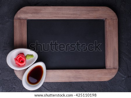 Soy sauce and ginger shape rose on vintage slate chalk board background. Asian style.  Selective focus. Top view - stock photo