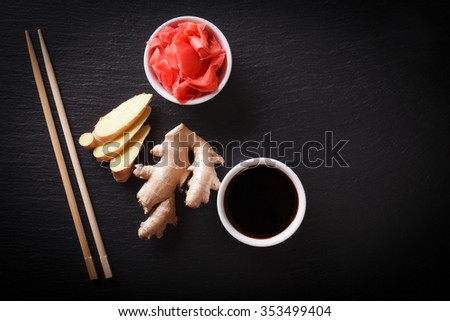 soy sauce and pickled ginger root on a slate blackboard. horizontal view from above