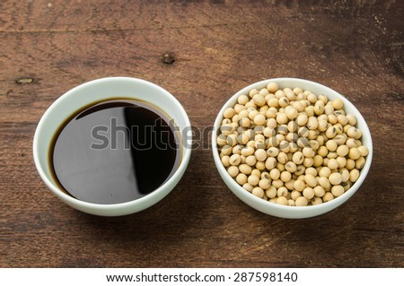 Soy sauce and soy bean in white bowl on wooden background. - stock photo
