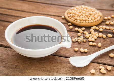 Soy sauce and soy bean on wooden background - stock photo