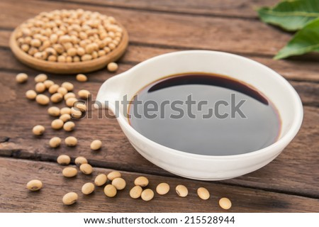 Soy sauce and soy bean on wooden table - stock photo