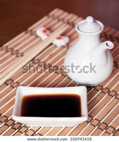Soy sauce for sushi on a bamboo pad - stock photo