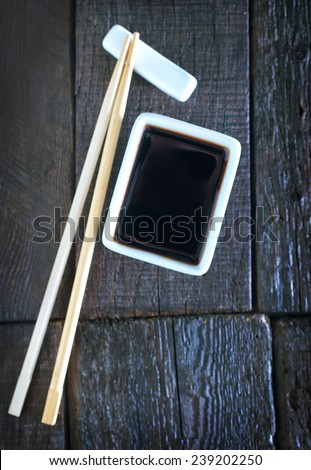 soy sauce in white bowl and on a table - stock photo