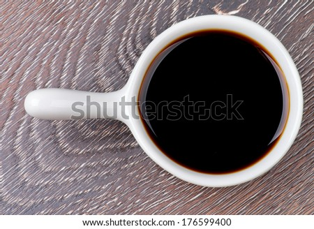 Soy Sauce in White Gravy Boat isolated on Wooden background. Top View - stock photo