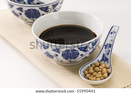 Soy sauce served in a chinese bowl. Soy beans in foreground. - stock photo