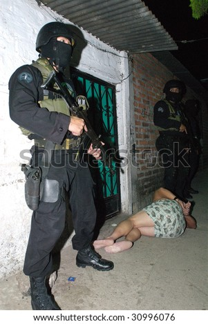 SOYAPANGO, EL SALVADOR, JAN 30: A Special Forces officer of the Grupo Reacion Policial (GRP) guards a gang suspect arrested at a raid against gang members on January 30, 2008 in El Salvador.