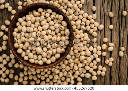 Soybean in wood bowl on wooden background.