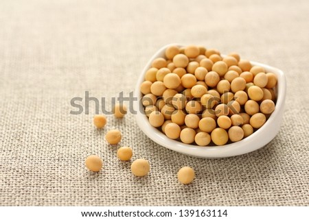 Soybeans in white ceramic bowl on sackcloth background - stock photo