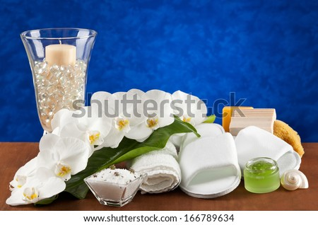 Spa accessories on wooden table with blue background