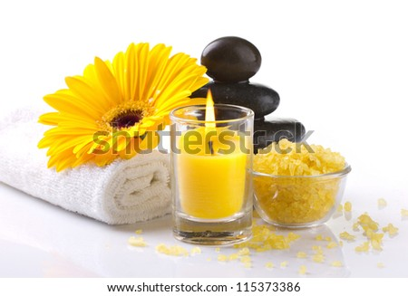 spa accessories, yellow flower and candles on white background
