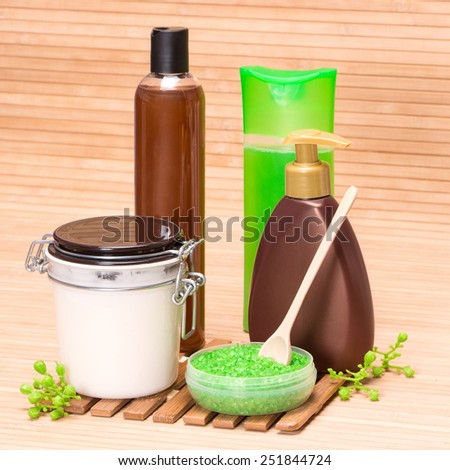 Spa and body care cosmetics: sea salt with a wooden spoon, body oil, shower gel, shampoo, liquid soap on wooden surface - stock photo