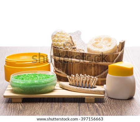Spa and pampering products and accessories. Green sea salt, massager, wooden basket with loofah, body scrubber and pumice, natural body scrub, skin care cream on wooden surface. Copy space on top