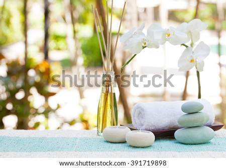 Spa and wellness massage setting Still life with aroma oil, towel and stones Outdoor summer background with fresh white orchid Copy space - stock photo
