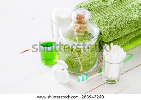 SPA and wellness - salt, towel, soap, cotton sticks and pads, tooth brush, floss, white wood background - stock photo