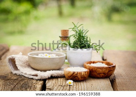 Spa and wellness setting with flowers, floral water and towel. Natural spa setting - stock photo