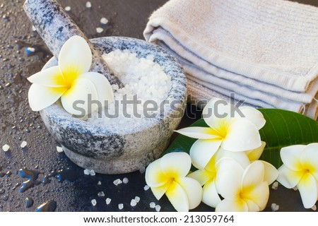 Spa and wellness setting with natural sea sat,  towels  and  frangipani  flowers - stock photo
