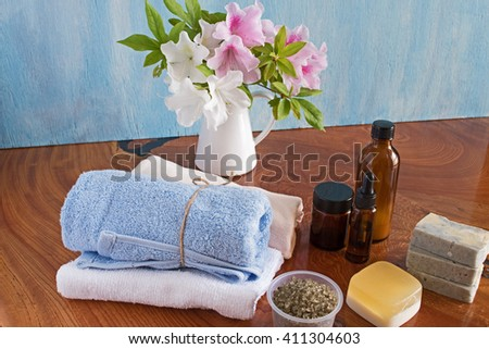 Spa and wellness setting with natural soap and orchid, sea salt, massage oils and soft towel.
