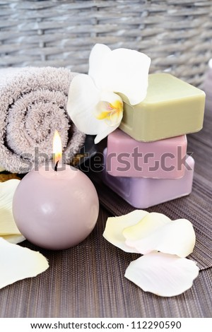Spa and wellness setting with natural soap, candles and towel. Beige dayspa - stock photo