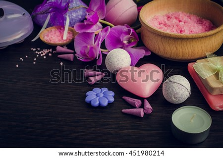 Spa and wellness setting with natural soap, sea salt and orchid in purple, pink and violet colors on dark wooden background. Aromatherapy concept. Selective focus. Copy space. - stock photo