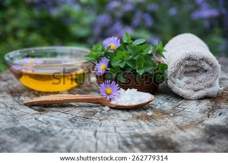 Spa and wellness setting with sea salt, oil essence, flowers and towels isolated. Relax and treatment therapy. White background. Selective focus. Close up.