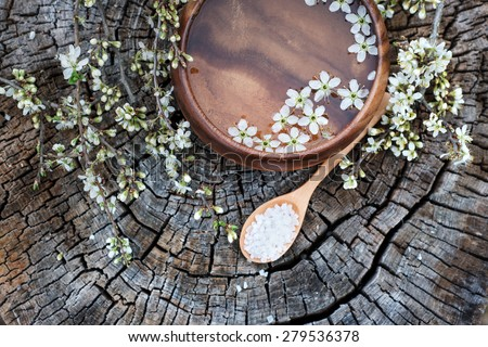 Spa and wellness setting with sea salt, oil essence, flowers and towels on wooden background. Relax and treatment therapy. Manicure and pedicure settings.  Spring season. Selective focus. Close up. - stock photo