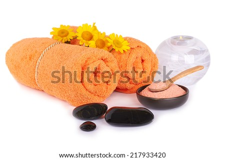 Spa and wellness setting with sea salt, stones, chamomiles flowers and towels isolated  - stock photo