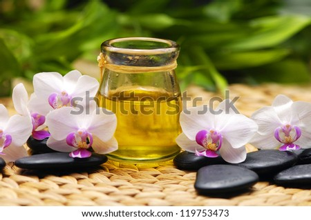 SPA background-candle with white orchid and stones ,massage oil with plant on mat
