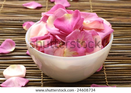 Spa background -Rose petal floating in water in bowl on mat - stock photo