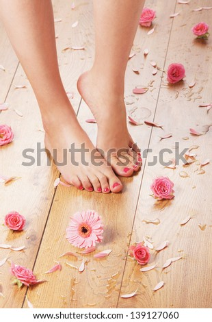 Spa background with a beautiful legs, flowers and petals - stock photo